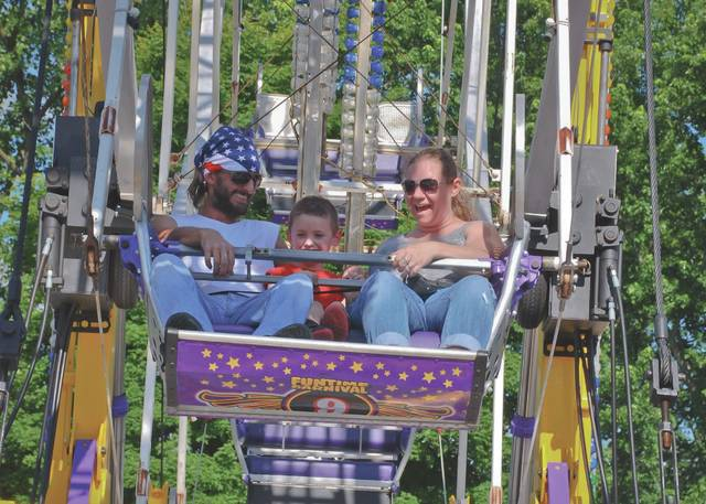 Before the lines became too long, many people arrived at the annual St. Mary's Festival in Delaware last year to ride the carnival attractions. From left to right, Joe Simpson, Levi Simpson and Jenny Young were some of the first people to hop aboard and ride the Ferris wheel to get a bird's-eye view of Delaware.