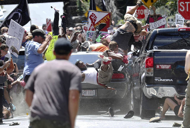 People fly into the air as a vehicle drives into a group of protesters demonstrating against a white nationalist rally Saturday in Charlottesville, Va. The nationalists were holding the rally to protest plans by the city of Charlottesville to remove a statue of Confederate Gen. Robert E. Lee. There were several hundred protesters marching in a long line when the car drove into a group of them.