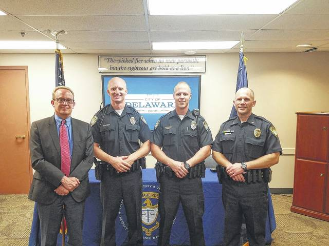 New police officers Travis Elkins, center left, and Bob Brown, center right, pose with Delaware City Manager Tom Homan, left, and Delaware Police Chief Bruce Pijanowski, right, after being sword in by Homan in July.