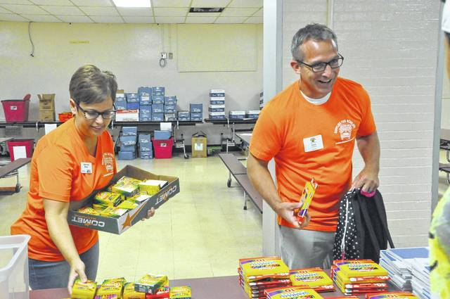 Schultz Elementary School Principal Travis Woodworth and volunteer Stephanie Manor gather school supplies for an elementary school student during Delaware City Schools' Supplies for Scholars event Monday morning. Delaware residents could bring their children for a free haircut and school supplies including a backpack during the annual event. School officials reported that 712 students stopped by for supplies Monday.