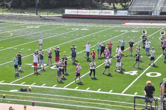 Students in the Delaware Hayes marching band practice their drill Thursday afternoon and play their instruments while moving to their next position. The band will practice their moves over and over until each member has the movements memorized for the entire show.