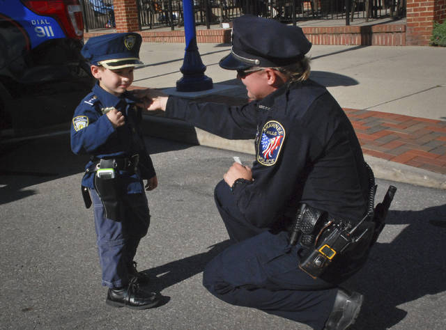 Making sure all is according to uniform codes Officer LC Goetz double checks Tanner Kongo's attire before Delaware's First Friday Picnic with a Cop. Kongo looked at every piece of police equipment and shook the hand of every police officer at the Friday evening event. Kongo said when he grows up he wants to be the chief of police just like his friend Delaware City Police Chief Bruce Pijanowski.