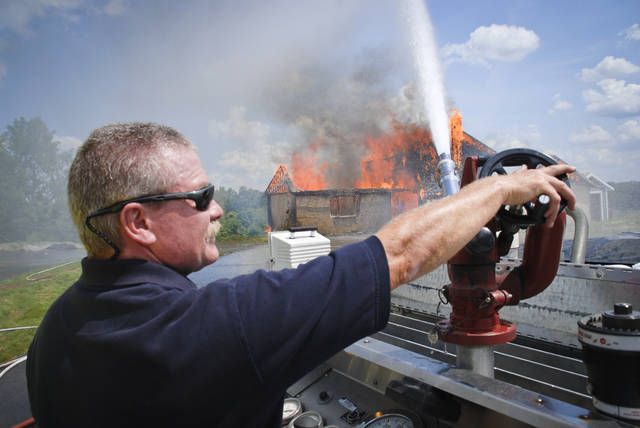 The City of Delaware Fire Department held a burn training exercise Monday inside a couple of houses on Stratford Road along U.S. 23. Capt. Jim Oberle of the Delaware Fire Department works the controls of a fire nozzle on the back of a tanker truck spraying the engulfed house to control the burn process.