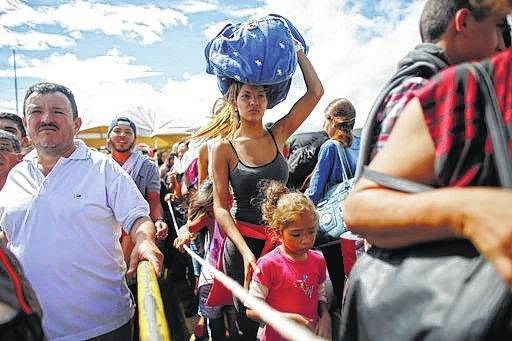 A woman carrying a bundle on her head waits in line to cross the border into Colombia through the Simon Bolivar International Bridge in San Antonio del Tachira, Venezuela. An estimated 25,000 Venezuelans trek across the international bridge into Colombia each day. Many come for a few hours to work or trade goods on the black market. But increasingly, they are coming to eat in one of a half-dozen facilities offering the increasingly hungry Venezuelans a free plate of food.