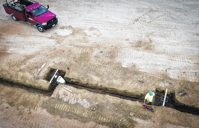 The land has been cleared and excavation for the foundation has begun on the new Buckeye Valley West Elementary School on State Route 257 at Bellpoint. Construction workers are placing concrete forms into the excavated line of the building's foundation.