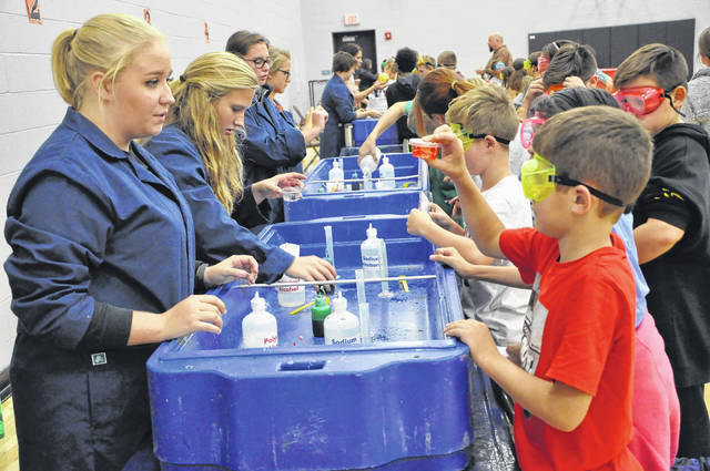 Woodward Elementary School fifth grader Steven Allsup, right, shows his slime mix to Lauren Rehm, a senior from the National Honor Society at Hayes High School, during COSI's chemistry day Thursday afternoon. There were numerous stations with different chemistry experiments. At the slime station, students could mix chemicals and pick the color slime they wanted before shaking the solution to thoroughly mix the chemicals, and then let it settle. Rehm told students it would take a while for the slime to settle and said they could get the slime back at the end of the day.