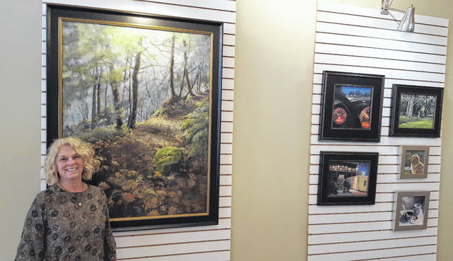 Sunbury resident Carolyn Heffelfinger poises next to some of her paintings on display inside her WORK of ART gallery located at 26 N. Sandusky St. in downtown Delaware. The gallery will open for a limited run beginning in November.