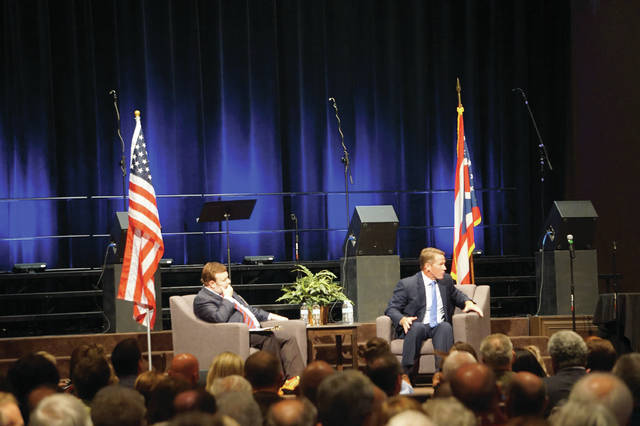 Fox News analyst Frank Luntz, left, looks on as Ohio Secretary of State Jon Husted tells a policeman that he'll stand up for them during an evening with the candidates for governor on Sunday at Genoa Church.