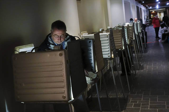 Voters fill out their ballots at a polling station, Tuesday, Nov. 7, 2017, in downtown Cincinnati. Ohio voters will decide ballot issues on Tuesday that would place limits on drug prices and expand victims' rights in criminal proceedings, along with several mayoral races. (AP Photo/John Minchillo)