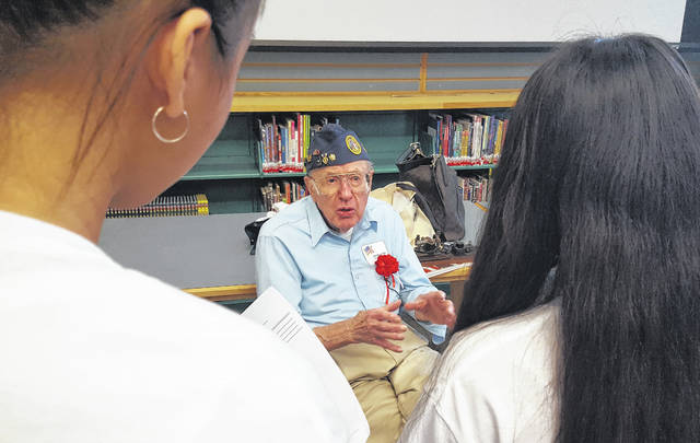 """World War II Army veteran John Bergmann speaks to several students in the library at Olentangy Hyatts Middle School. Bergmann was one of dozens of veterans who spoke to eighth-graders on Friday during the school's annual """"Living History Day."""""""