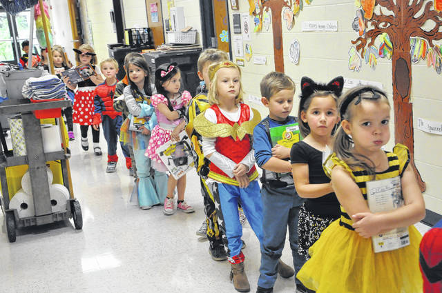 Students in Amanda Bartz's kindergarten class at Carlisle Elementary School walk to class in Halloween costumes Tuesday afternoon. Parents volunteered to conduct crafts and games for their students. Costumes ranged from superheroes, to video game characters, to firefighters and fairy-tale characters. Students at Smith and Schultz elementary schools also participated in Halloween activities on Tuesday.