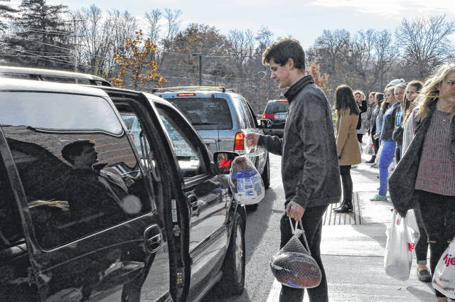 A student at Hayes High School puts a turkey in a local resident's van Tuesday afternoon during the Fight Against Hunger Games event. More than 125 turkeys and hams will be donated to local families, court officials said Tuesday.