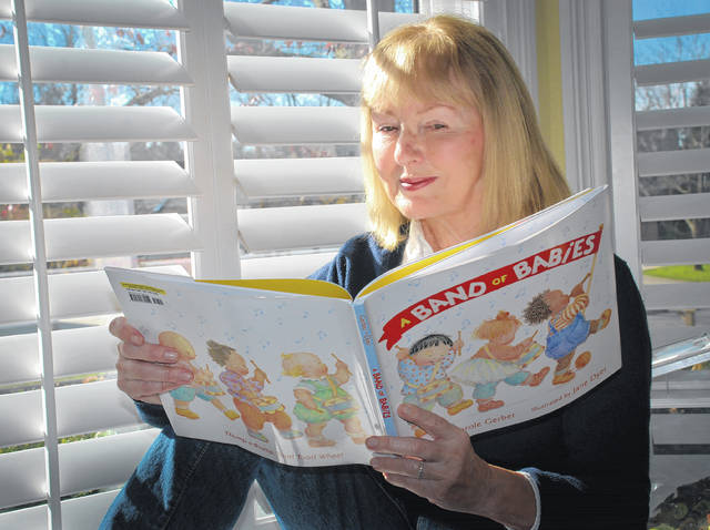 Award-winning author Carole Gerber sits in her dining room bay window leafing through the pages of her book &#8220;A Band of Babies.&#8221; The book was announced as one of Amazon&#8217;s <a href=&quot;https://www.amazon.com/b/ref=s9_acss_bw_cg_BOTYkid_2a1_w?node=17296347011&amp;pf_rd_m=ATVPDKIKX0DER&amp;pf_rd_s=merchandised-search-3&amp;pf_rd_r=XYDGR59HRAVWNJ57W2GS&amp;pf_rd_t=101&amp;pf_rd_p=08d8d9a7-6964-4761-b65c-474e8a731267&amp;pf_rd_i=17296227011&quot;>&#8220;20 Best Children&#8217;s Books of 2017</a>&#8221; last week.
