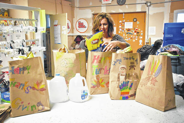 The Common Ground Free Store will be open Saturday, Nov. 25 from 9:30 to 11:30 a.m. to serve a warm meal and provide take-home bags of food to those who might go without a meal between Thanksgiving Day and Monday. Executive Director Sharon Griner fills bags with donated food items. The bags were decorated by women from the Horizons Program at the Ohio Reformatory for Women.