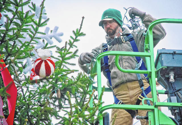 Main Street Delaware volunteers spent Wednesday decorating the 30-foot tall spruce tree that currently sits on the corner of South Sandusky Street and West William Street. Colin Shea of Rine Landscaping Group used a lift to string the lights, which he said he tested before putting them on the tree. The tree-lighting ceremony is scheduled for 6:30 p.m. on Friday, Dec. 1 during First Friday.
