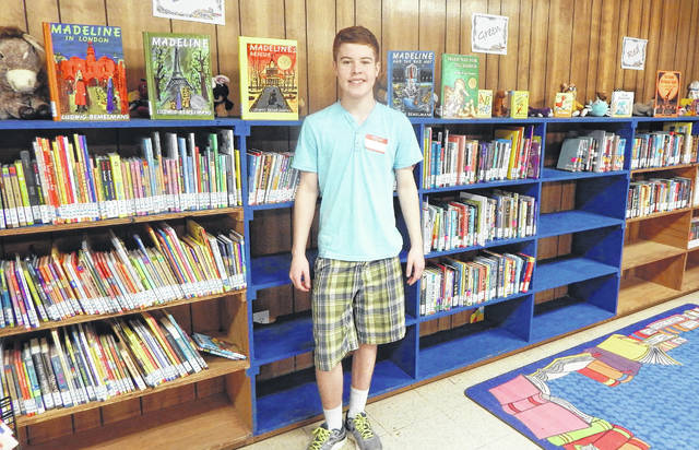 Heber Fuller, a freshman at Olentangy Orange High School who dedicated his Eagle Scout Service Project to collecting books for Hull-Daisetta Elementary School in Hull, Texas, stands in front of some of the nearly 18,000 books he helped collect and unpack at the school's temporary school building in Hardin, Texas. The elementary lost nearly 12,000 library and classrooms books during Hurricane Harvey.