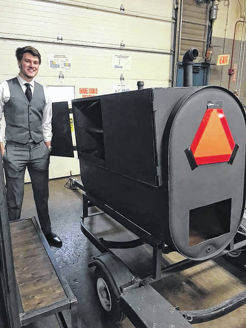 Delaware Area Career Center welding senior Nick Gerold stands next to his completed senior project, a smoker made from an old fuel tank and jet ski trailer. Gerold said the project took about 40 hours to complete.