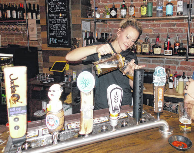 Delaware native Amanda Sykes, co-owner and bartender at The Flying Pig Ale House in downtown Delaware, pours a glass of beer from a french press that was used to infuse the beer with dry hops.