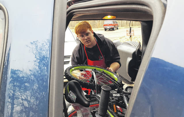 Volunteer Bailey Myers helps load a new bicycle into the trunk of a SUV on Friday during distribution day for The Salvation Army of Central Ohio-Delaware County's annual Christmas Assistance Program. Myers, along with numerous other volunteers, spent Friday packing vehicle after vehicle with items at The Salvation Army Delaware Worship and Community Center, 340 Lake St.