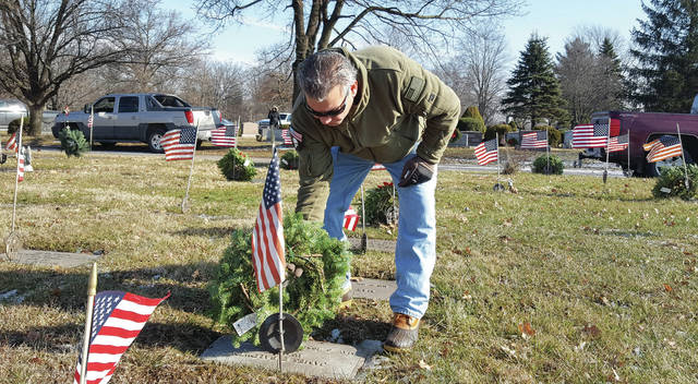 U.S. Air Force veteran Ed Correa, who served his country for over two decades, places a wreath on the grave of a veteran buried in Oak Grove Cemetery in Delaware. Correa, a resident of Marion, was one of countless volunteers who showed up Saturday to help place 180 wreaths on the graves of veterans as part of the annual Wreaths Across America event. Held nationwide in approximately 1,000 cemeteries, the local event was planned by the Vietnam Veterans of America Chapter 1095. Correa said he is making it his mission to bring the Wreaths Across America event to the Marion Cemetery next year.