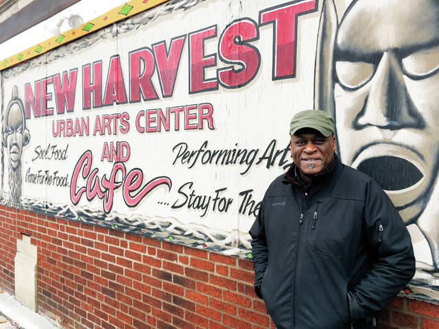 In this Monday, Dec. 18 photo, Columbus community activist Kwodwo Ababio stands outside his New Harvest Urban Arts Center and Cafe in Columbus, Ohio. The city's soaring homicide rate hit home for Ababio recently when a former foster son was shot and killed.