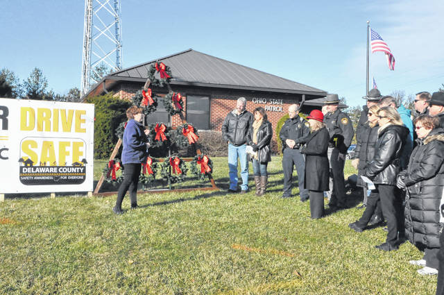 SAFE Delaware Coordinator Jackie Bain speaks to a group of community members, law enforcement and families of crash victims Wednesday morning in front of the Delaware Post of the Ohio Highway Patrol before the group pinned names of the deceased to each of the wreaths.