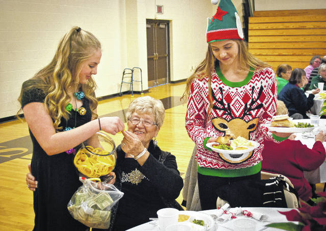 Connie Herd, center, is served lunch by her two granddaughters Hayle Romo, left, and Cameron Romo, right, during the annual Senior Citizens Concert and Luncheon at Buckeye Valley High School. The event was started in 1984 with 15 grandparents and has expanded to 300 senior citizens each year.