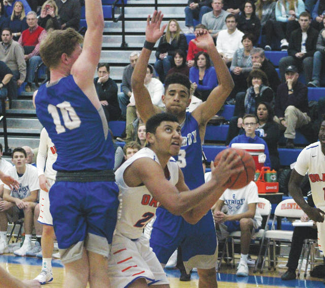 Olentangy's Orange's Jalen Bethel, center, works against Liberty's Ben Roderick, back, and Grant Wilson in the post during the first half of Friday's OCC showdown in Lewis Center.
