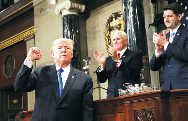 President Donald Trump gestures as he finishes his first State of the Union address in the House chamber of the U.S. Capitol to a joint session of Congress Tuesday in Washington, as Vice President Mike Pence and House Speaker Paul Ryan applaud.