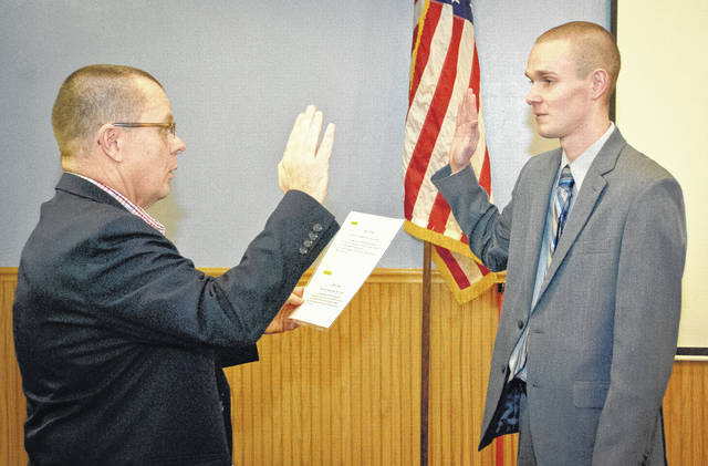 Before Genoa Township's reorganization of the trustee board Thursday, Fire Chief Gary Honeycutt introduced and recommended Ian Fellers to be hired as a full-time firefighter/paramedic with the township's department. Fiscal Officer Patrick Myers, left, swore in Fellers once the motion to hire him as a full-time firefighter for the township was approved by trustees.