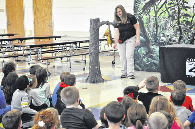 First graders at Schultz Elementary School marvel as a handler from the Columbus Zoo and Aquarium demonstrates the kinkajou's prehensile tail and its ability to hang to grab food. Kinkajous, which are related to raccoons, live in the rainforests of Central and South America and spend most of their time in trees. Students were also visited by a penguin and a legless lizard and learned about their habitats and environments.