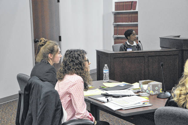 Mackenzie Collett, left, and Mallorie Watts, right, attorneys on the Delaware Hayes mock trial team, listen as one of their witnesses and teammates, Jackson Collins, on the stand, is cross examined by another team. The teams competited in several legal battles and had to represent the case from both sides.