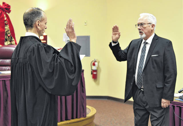Delaware County Court of Common Pleas Judge David Gormley, left, administers the oath of office to Jon Bennehoof on Tuesday at the Powell Municipal Building. Council member Bennehoof was sworn in as the city's new mayor.