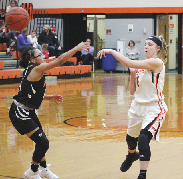 Hayes' Piper Adkins, right, fires a pass into the post during the first half of Wednesday's non-league showdown against Whitehall. The Rams' Sahlena Harvey was defending on the play.