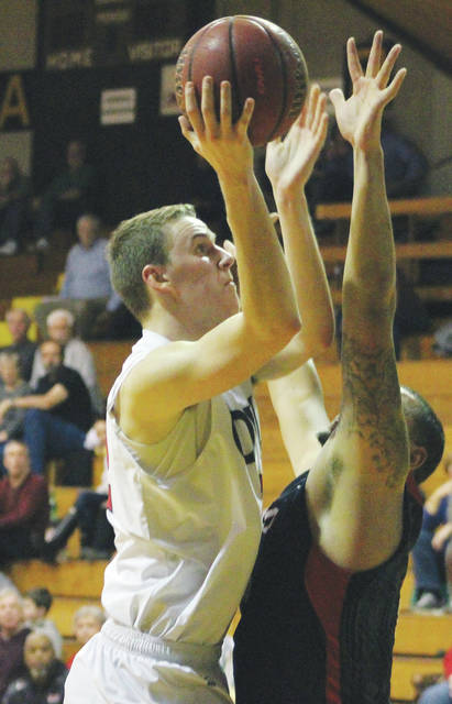 Ohio Wesleyan's Grant Gossard puts up a shot over Hiram's Kelvin Jones during the first half of Wednesday's NCAC showdown at Branch Rickey Arena.