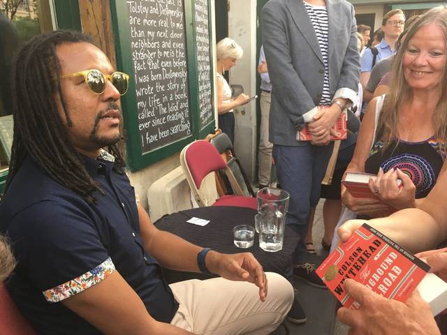 """In this June 20, 2017 photos, Novelist Colson Whitehead speaks to fans after discussing his Pulitzer prize-winning book """"The Underground Railroad"""" at the English-language bookstore Shakespeare and Company in Paris. Travelers to Paris can create a different type of itinerary exploring African-American connections to the City of Light. Some of the United States' greatest black intellectuals and performers sought an escape here from the racism of 20th century America, and with a little homework, you can retrace their footsteps. (AP Photo/Russell Contreras)"""