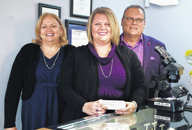 Standing behind one of their jewelry cases in their new location are, left to right, Sherry, Kristy and John Fetzer of Delaware Diamonds. Over the holidays, the family business moved from downtown Delaware to 652 W. Central Ave., Suite 80.