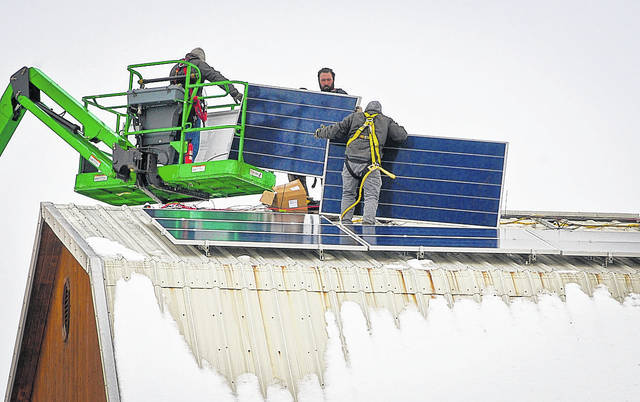 """Battling the elements to install an array of 156 solar panels on the roof of Stratford Ecological Center's barn was no easy task for a crew of technicians with Third Sun Solar from Athens. """"They had a snow blower up there to get all the snow and ice off of the buildings,"""" said R. David Hoy, development director of Stratford. On Friday, the crew gained a break in the weather to start putting the panels into place on the barn and machine shed."""