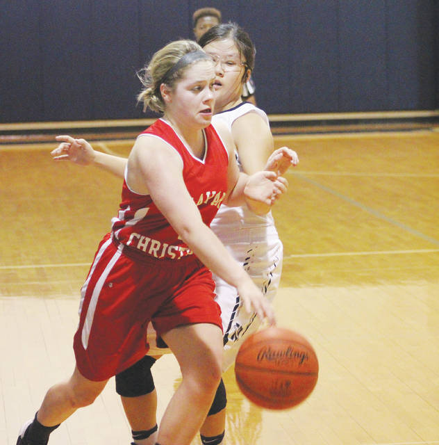 Delaware Christian's Anna Fuller drives by Wellington's Eli Burkhardt during the second quarter of Wednesday's Division IV District Tournament game in Columbus.