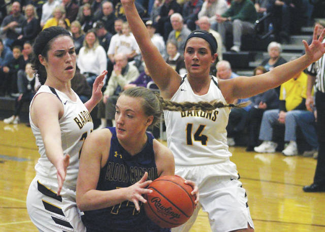 Buckeye Valley's Hannah Cowan, left, and Alaina Radcliffe trap Bloom-Carroll's Haley Vollmer under the hoop in the first half of Friday's Division II district championship game in Westerville.