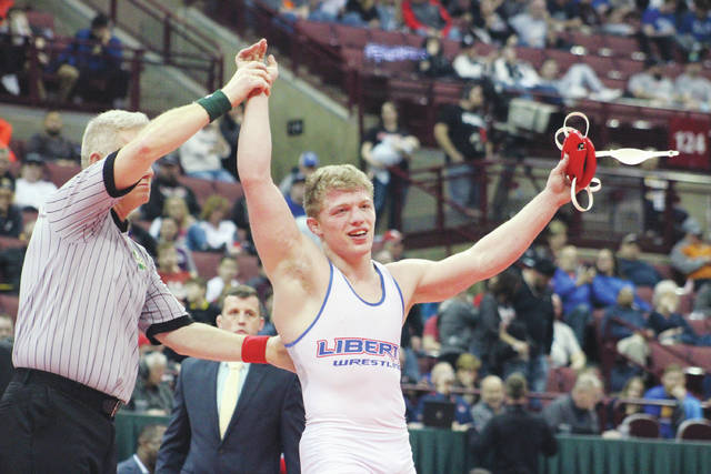 Liberty's Carson Kharchla celebrates after winning a state title at 170 during the OHSAA Division I Individual State Wrestling Tournament Saturday at OSU.