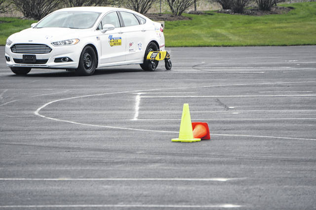"""A """"skid car"""" — a Ford Focus equipped with hydraulics to provide less traction for the rear wheels — drives on a course set up in the parking lot of A.D. Farrow in Sunbury on April 17."""