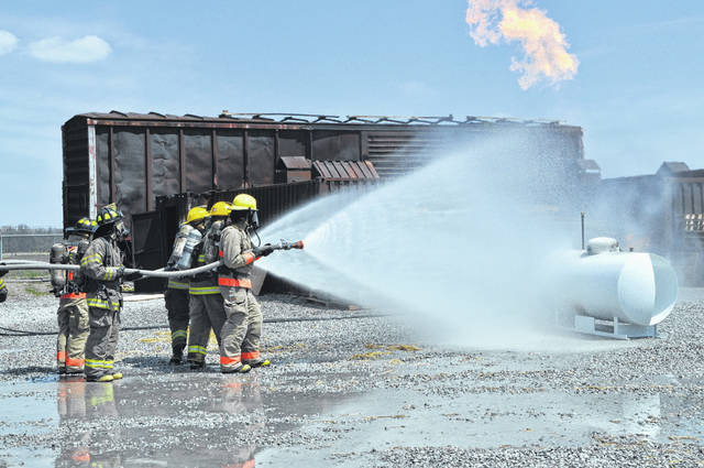 Firefighting students at the Delaware Area Career Center advance toward a propane fire Friday at the DACC North Campus.