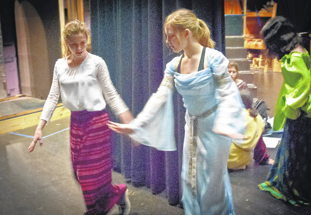 """Backstage on Thursday evening at Buckeye Valley High School, students Alexa Draper, left, and Clare Digrandi, right, practice their dance steps before going on stage to rehearse for """"Once Upon a Mattress."""" In a last minute shakedown of the new lighting system, Peter Naumenko, a lighting specialist with Demmer Solutions Audio and Video of Columbus, shows Robin Wilson, a Buckeye Valley High School student, how to use the new touchscreen system. """"Once Upon a Mattress"""" will be the first production to use the system."""