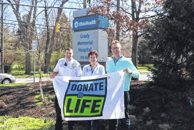 Pictured holding a Donate Life flag outside OhioHealth Grady Memorial Hospital in Delaware are, left to right, George Organ, protective services supervisor at Grady; Denise Anderson, nurse administrator at Grady; and Andrew Mullins, director of Partner Services at Lifeline of Ohio.
