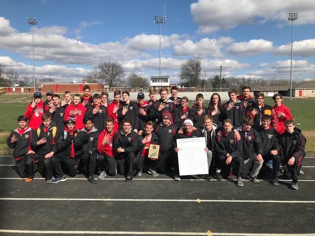 Members of the Big Walnut boys track and field team celebrate after winning their fourth straight Big Walnut Red Edwards Relay title Saturday in Sunbury.