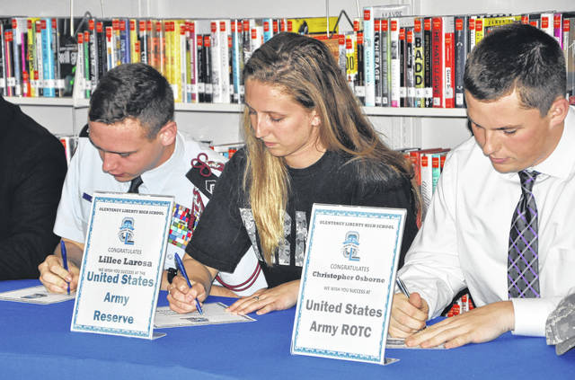 """Pictured signing their """"letters of intent"""" during Olentangy Liberty High School's first-ever Military Signing Day on Wednesday are, left to right, Madison """"Mason"""" Hart (Air Force ROTC), Lillee Larosa (Army Reserve) and Christopher Osborne (Army ROTC)."""