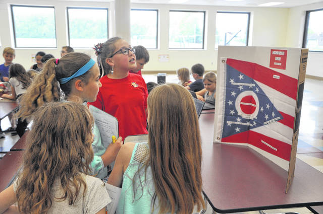 Schultz fourth-grader Amelia Pflaum gives a presentation about Ohio's state flag Monday afternoon during the Ohio History Fair. Students at Schultz toured the fair and had a list of the types of presentations they were supposed to find, like a scavenger hunt, to encourage them to hear as many presentations as possible.