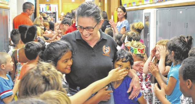 """Retiring cashier Sharon Wolford gets a hug from two students at Woodward Elementary School Wednesday during the """"clap out"""" for fifth-grade students. Wolford, who is retiring after 38 years, led fifth-graders on a walk through the halls while their schoolmates cheered them on."""