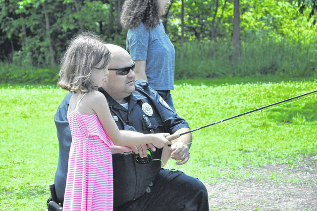 City of Delaware School Resource Officer John Hartman teaches second-grader Ella Mowery how to fish at Blue Limestone Park on Tuesday. The police department will host the Fish with a Cop event on July 7 from 8 a.m. to 12 p.m.